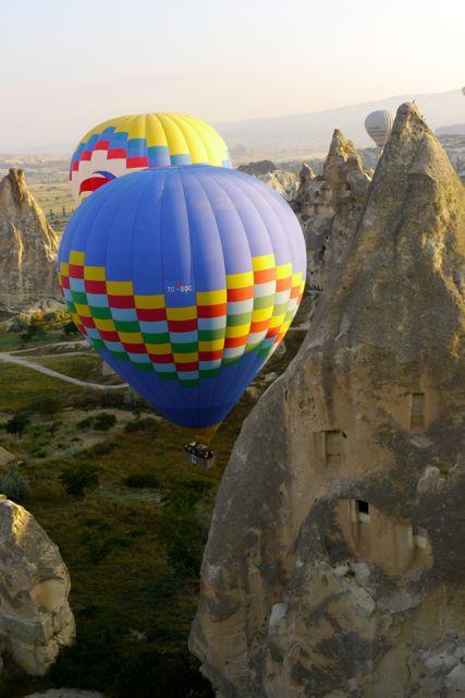 De ballonvaarders sturen heel dicht langs de rotsen.