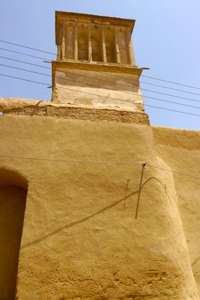 een badgir steekt boven de huizen uit.
